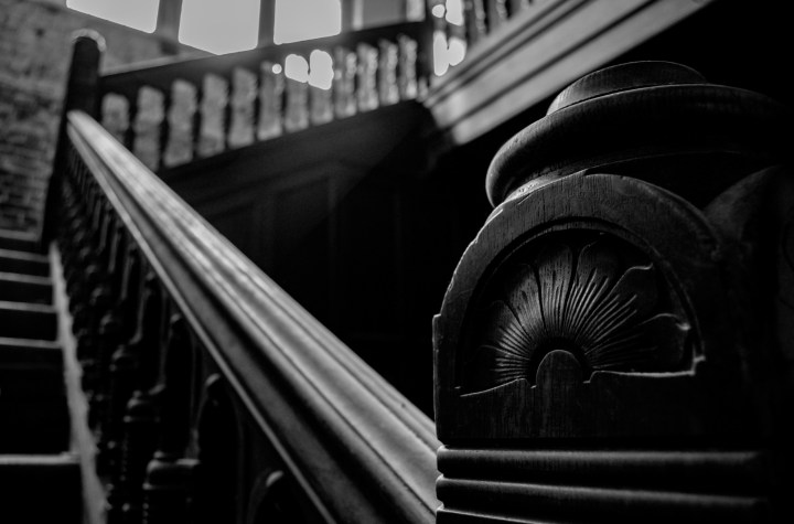 Black and white image of an ornate carved handrail with the stairs leading upward and turning to the right. One stair is missing, but it is hard to see unless you are looking for it.