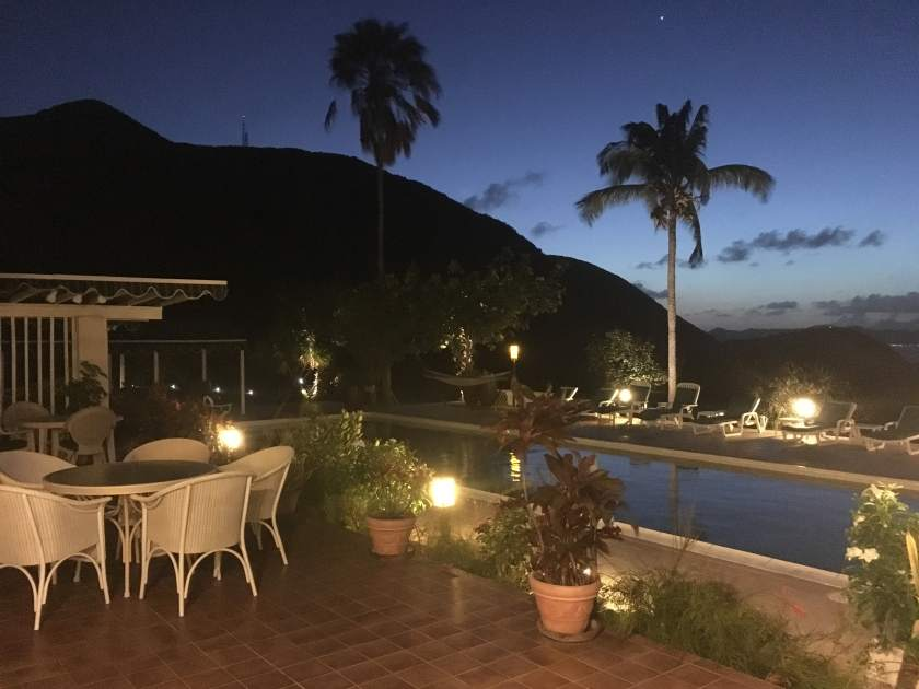 Mount Nevis Hotel Pool at Night with ample seating, lounge chairs, hammocks, and plenty of lights.