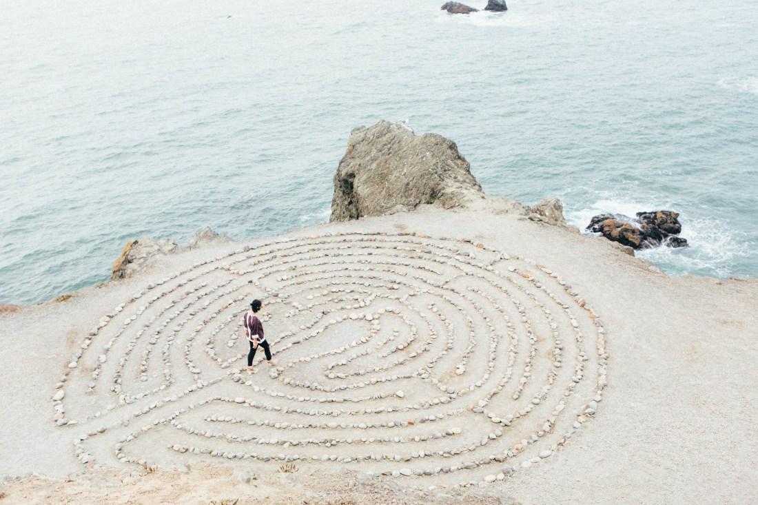 A girl walking through a maze on a beach