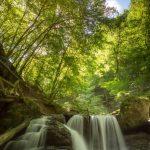 Imposante waterval op de Ehrbach, een riviertje in de Duitse Hunsrück. Het water stort zich in verschillende richtingen over de rotsblokken naar beneden. De lange sluitertijd geeft extra dynamiek aan het snel bewegende water. Het zonlicht zorgt voor een frisgroen bladerdek in het bos in de achtergrond. De staalblauwe lucht zorgt voor een zomerse sfeer.