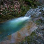 Een van de vele watervalltjes op de Ninglinspo, een Ardeens bergriviertje. De diepblauwe kleur van het water zorg voor een koud tint in het beeld. De lange sluitertijd geeft een bijzondere dynamiek aan het waterbad aan de voet van de waterval.