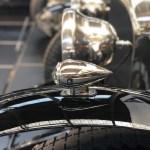 Het zwarte spatbord met daarop een blinkende gechromeerde richtingsaanwijzer boven de band van een voor-oorlogse Bentley. Op de achtergrond zie je de onscherpe koplampen van deze auto en van een tweede Bentley die ernaast staat.
