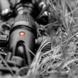 Zwart wit beld van een statief in het gras, met één gekleurd accent: het rode logo van het Manfrotto statief