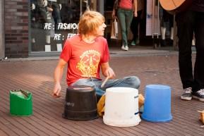 Nee, hij mist niet. Het gat tussen het groene blik en de bruine emmer had een doel: hij gebruikte de straat als onderdeel van zijn bucket-drumkit.