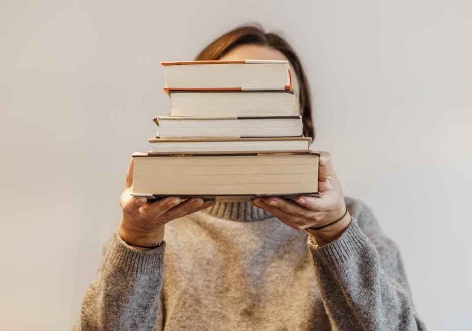 faceless student with pile of books on light background