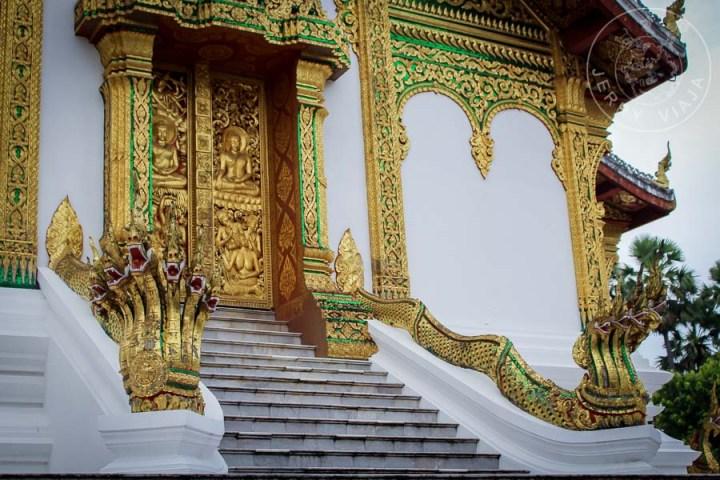 Entrada a templo budista con estatuas de nagas a los costados de la escalinata