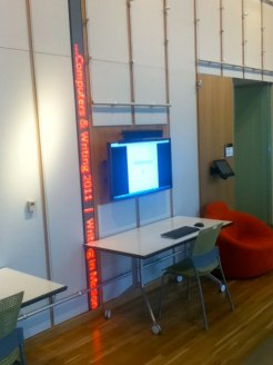 A flatscreen computer monitor, next to an LED tickertape that runs up the wall.