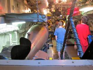 A bunk hangs on a chain just a few inches above a torpedo. This was considered one of the better places to sleep, as it's far forward of the engine room -- which was very hot.