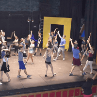 Performers rehearsing a dance scene from West Side Story on the stage of the Geyer Performing Arts Center