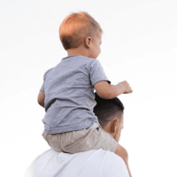 A father gives his happy toddler a ride on his shoulders.