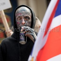 Man with fascist tattoo including C18 on his eyelid and a swastika on forehead drinking illegally during an EDL national demonstration in Worcester, Worcestershire.