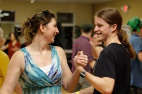 "Deidra Swails and Joel Dettweiler smile as they allemande as part of a dance called ""the little black dress""."
