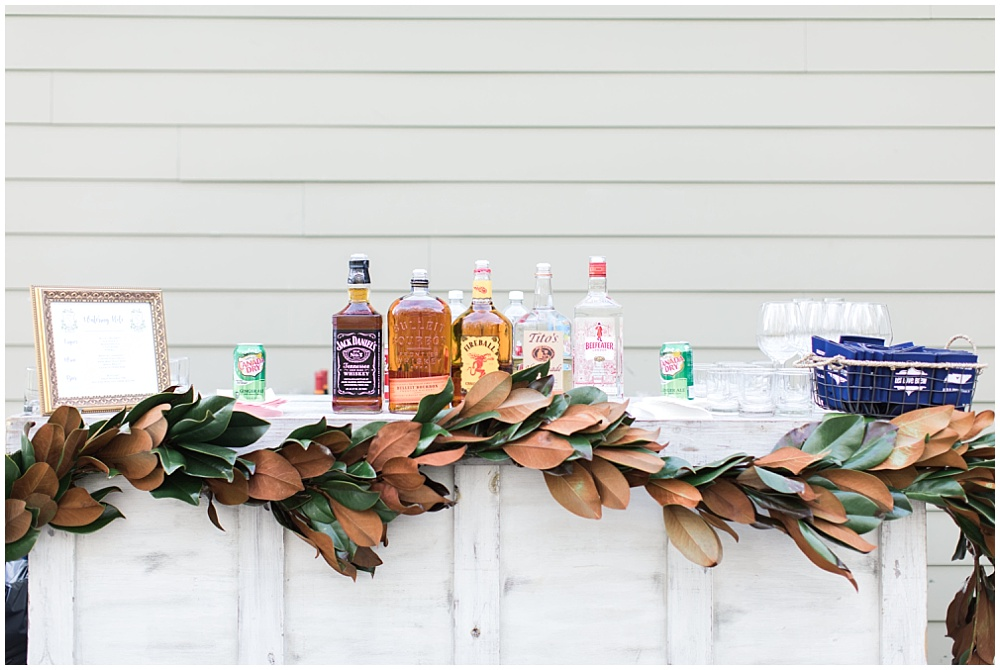 6 ways to elevate your wedding details; draped greenery; magnolia garland; farmhouse-style bar; draped magnolia leaves; bar details; rustic bar; southern bar; southern accents