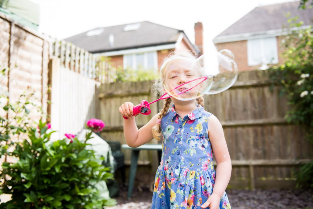Girl blowing large bubble back garden