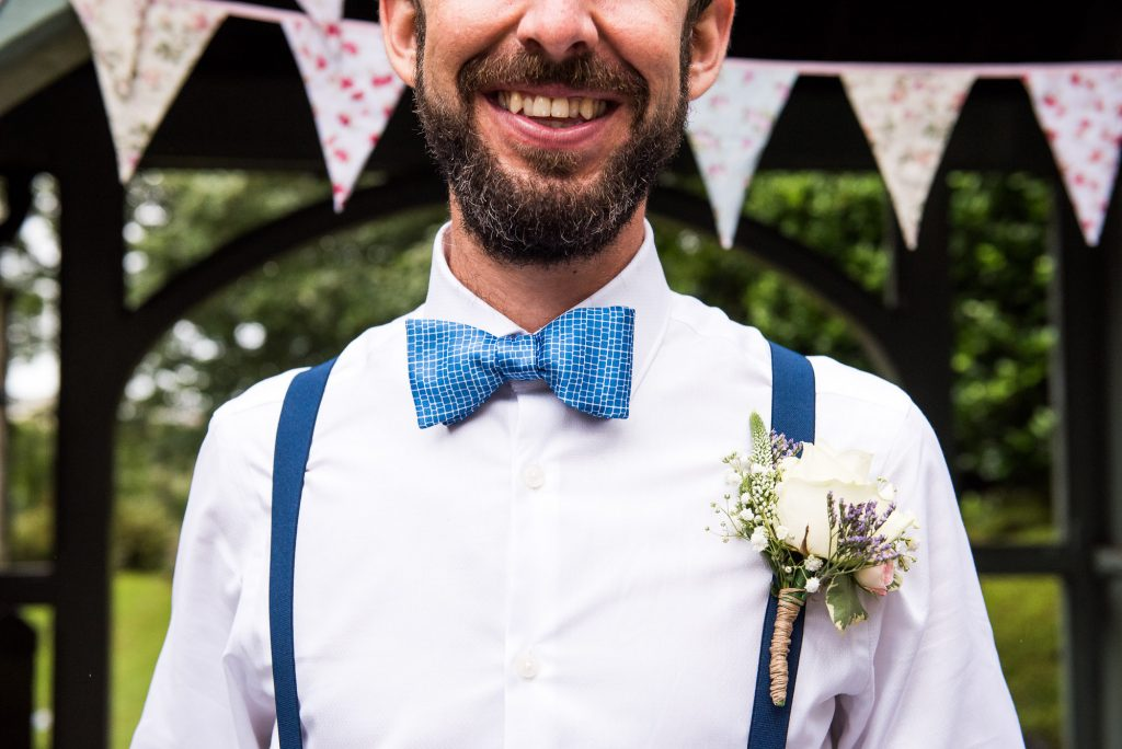 Groom wearing blue bow tie with bunting to decorate beach wedding Cornwall