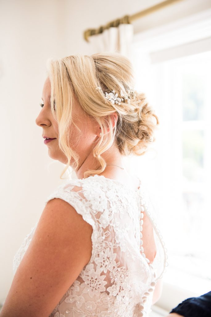 Elegant bridal hair by Lucy Alexander with flower detail