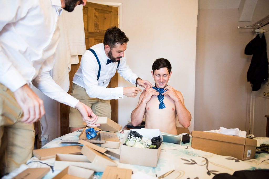 Fun pre wedding photography during groom prep with groomsmen Cornwall