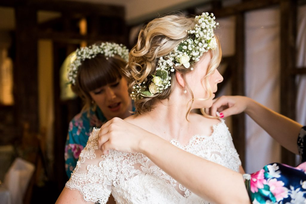 Bride wearing lace dress with floral crown during bridal prep Cornwall