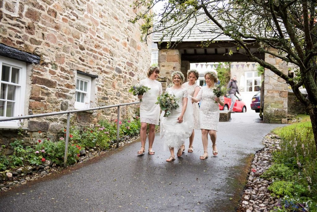 Bride with bridesmaids wearing lace white dresses walk together Cornwall