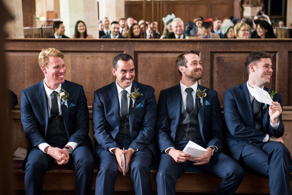 Smiling groomsmen wearing Calvin Klein navy suit Norfolk wedding photography