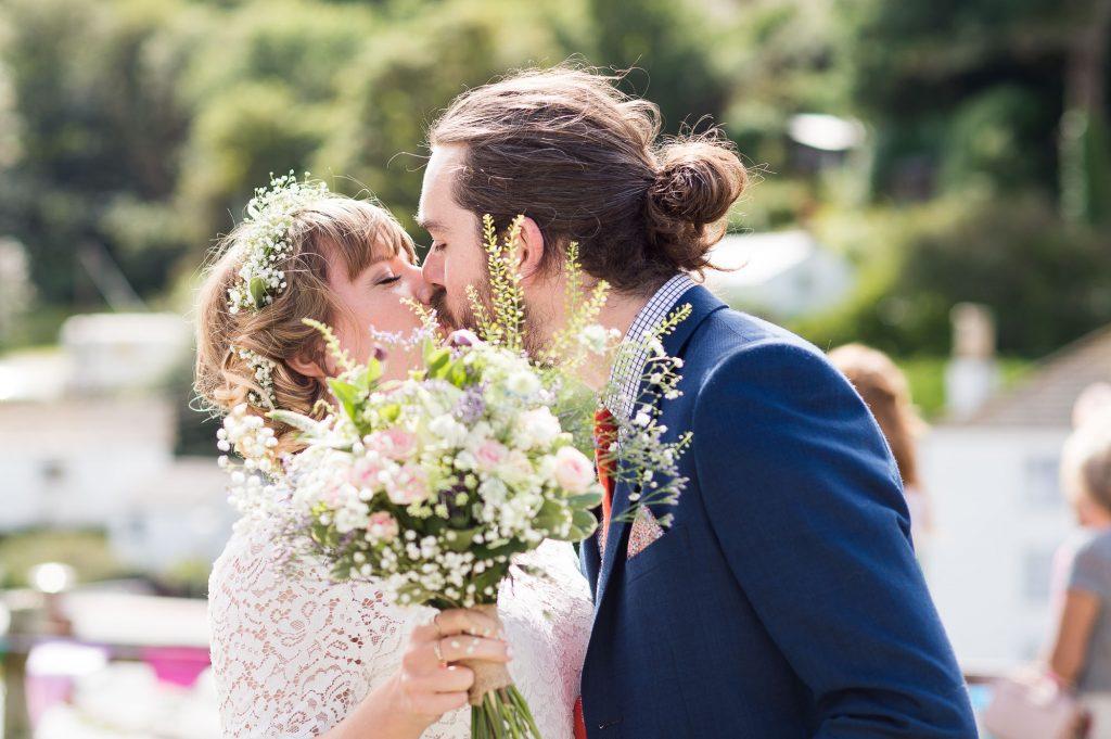 Bridesmaid kissing husband Cornwall beach wedding