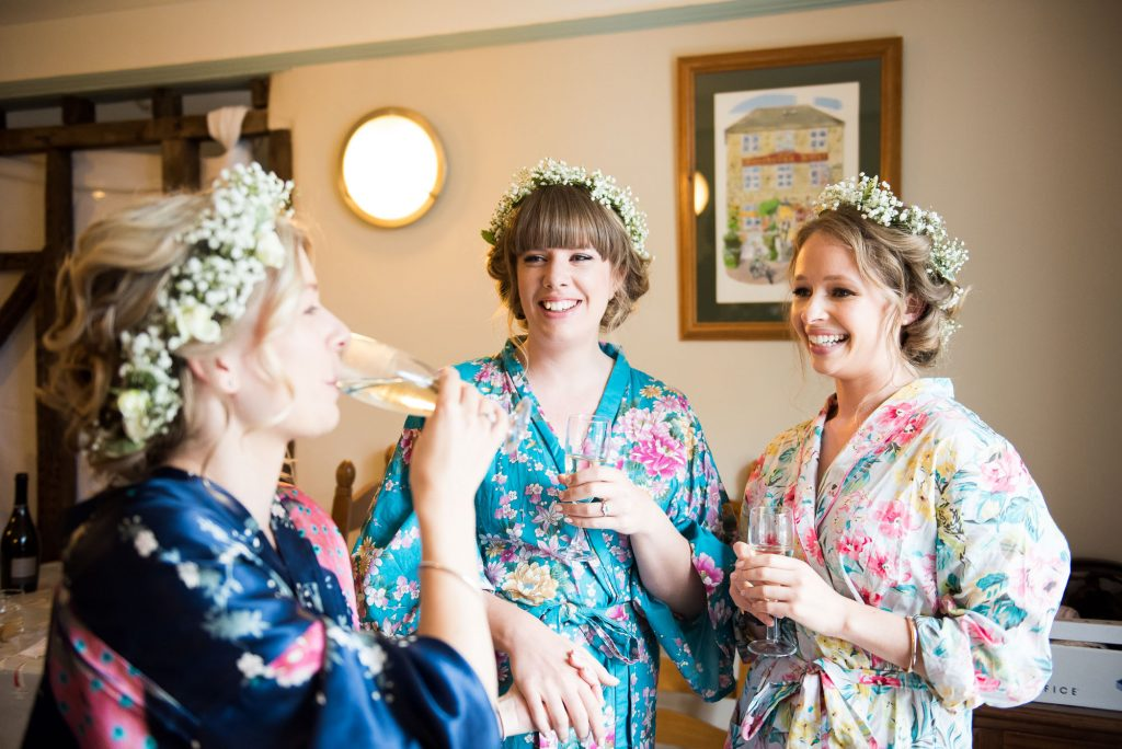 Bride with bridesmaids drink champagne wearing floral robes and floral crowns pre wedding photography Cornwall