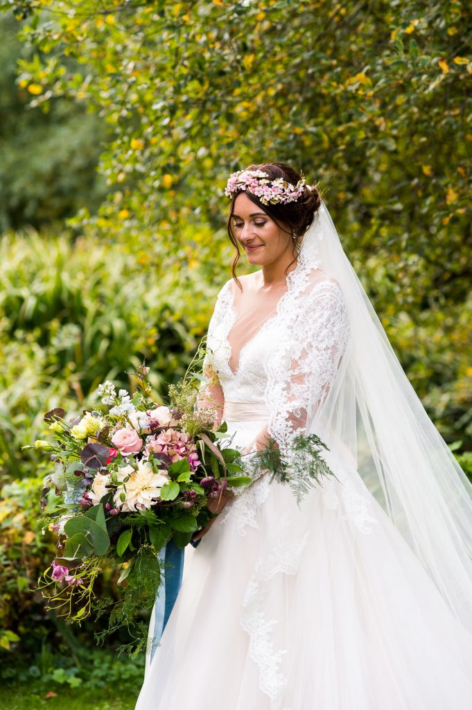 Jay West Bride wearing floral crown with veil Norfolk Barn wedding