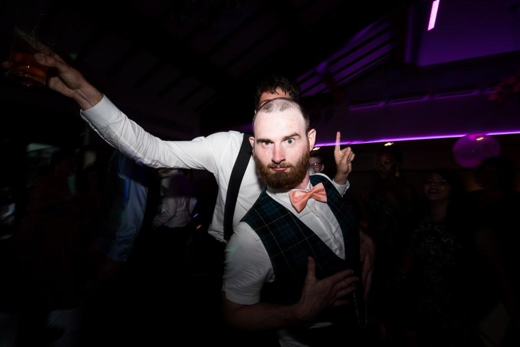 Funky groom with best man on dance floor Berkshire
