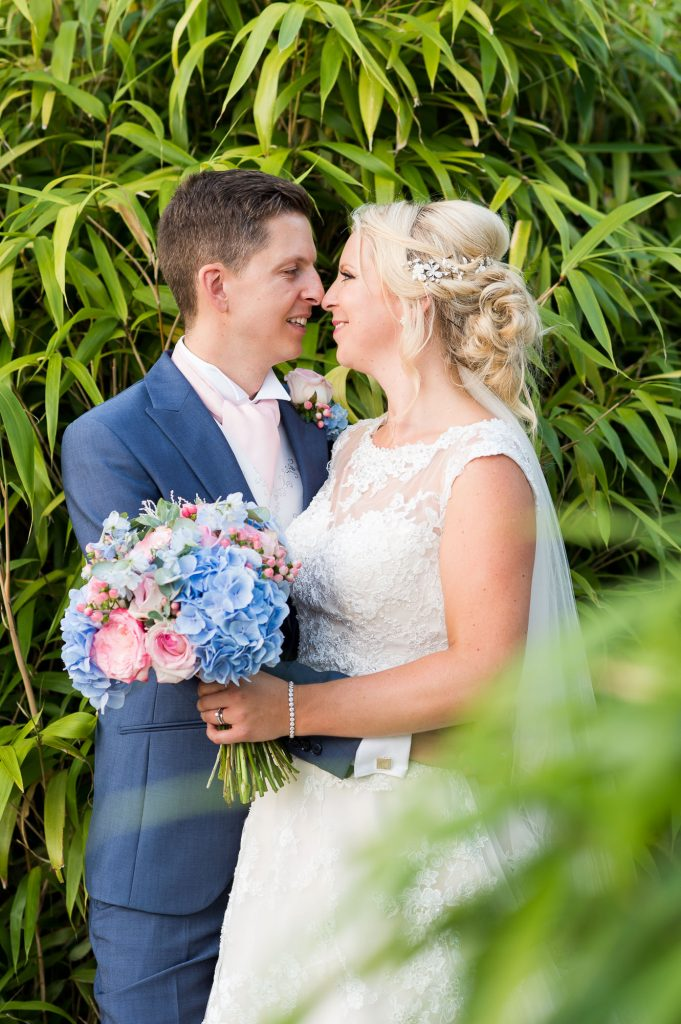 Groom wearing navy blue suit with Ronald Joyce bride