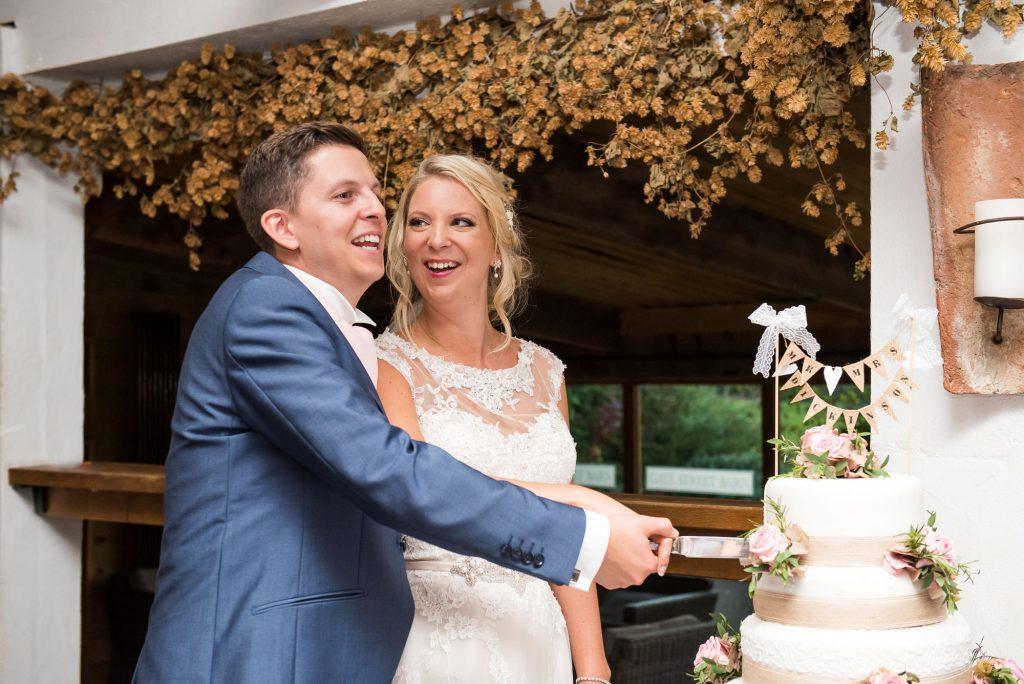 Bride with groom cut wedding cake by Alice Michieli