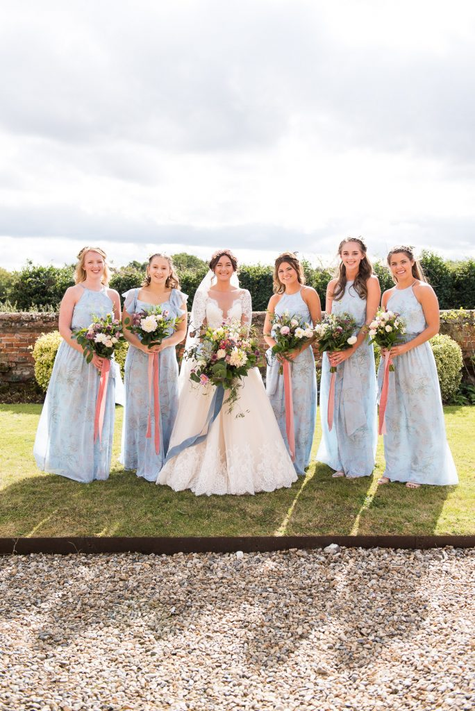 Bride with pastel blue bridesmaids Norfolk Barn Wedding