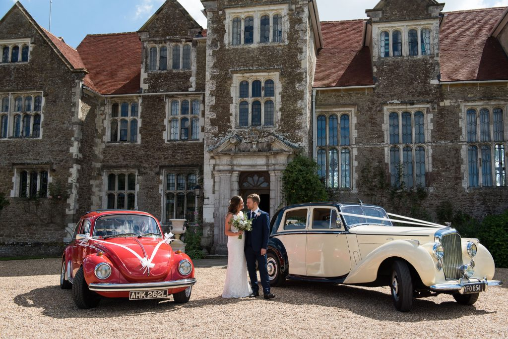 Traditional vintage cars outside Loseley Park with the newlyweds
