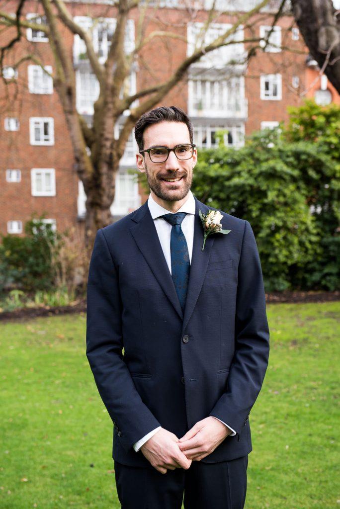 Wedding portrait of stylish groom in navy blue suit