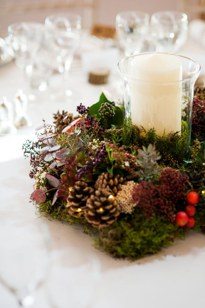 Ashridge House Wedding. Natural Wedding Photography. Natural floral tone centre pieces with pine cones, winter berries and moss.