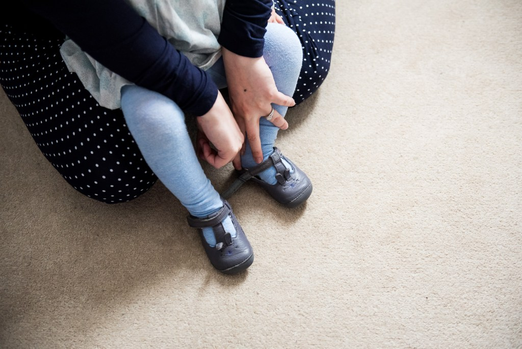 Surrey Family Photography, Family photographer, Candid moment of mother putting on her babies shoes