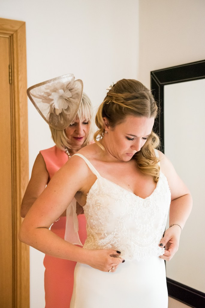 Mother Of The Bride Helps Her Daughter Into Catherine Deane Bridal Dress