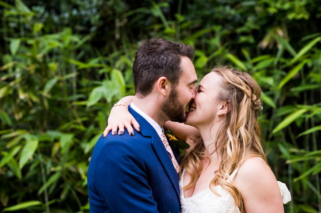 Outdoor Wedding Ceremony, Surrey Wedding Photography, Bride and Groom Share a Kiss With Bamboo Forest Backdrop