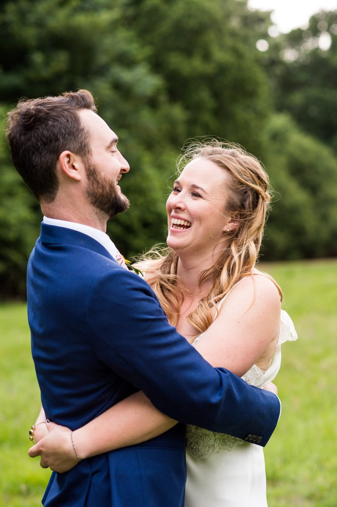 Outdoor Wedding Ceremony, Surrey Wedding Photography, Bride and Groom Smile and Laugh Together as They Embrace