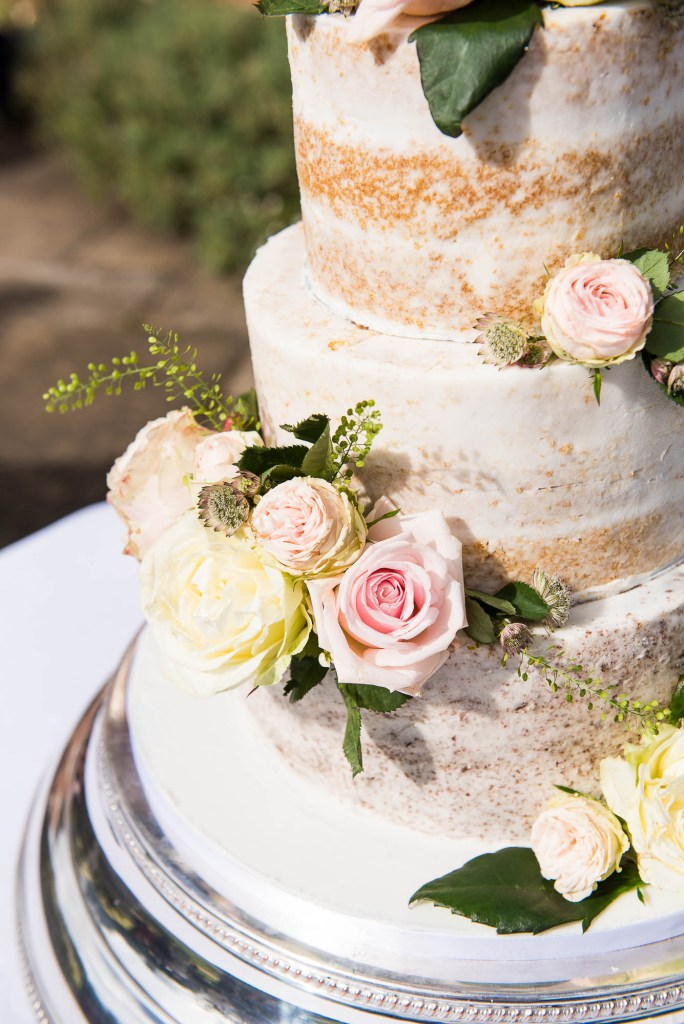 Outdoor Wedding Photography Surrey, Beautiful Three Tier Wedding Cake With White Icing and Fresh Flowers
