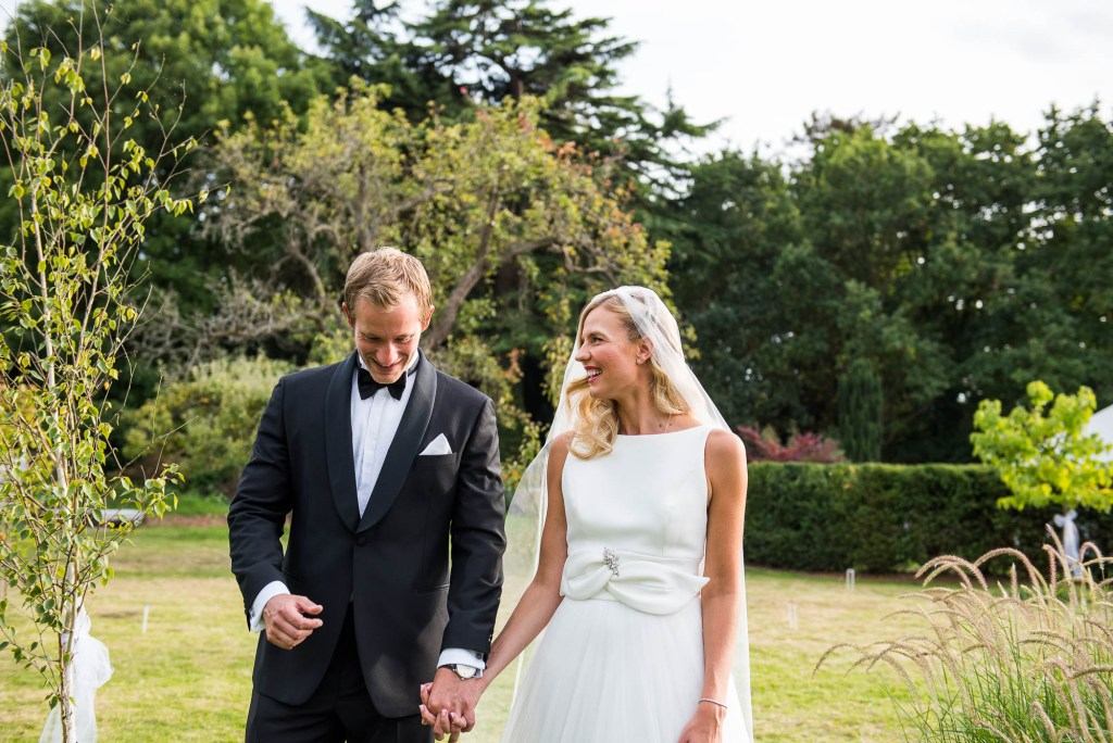 Outdoor Wedding Photography Surrey, Elegant Bride and Groom Smiling Naturally As They Walk Together