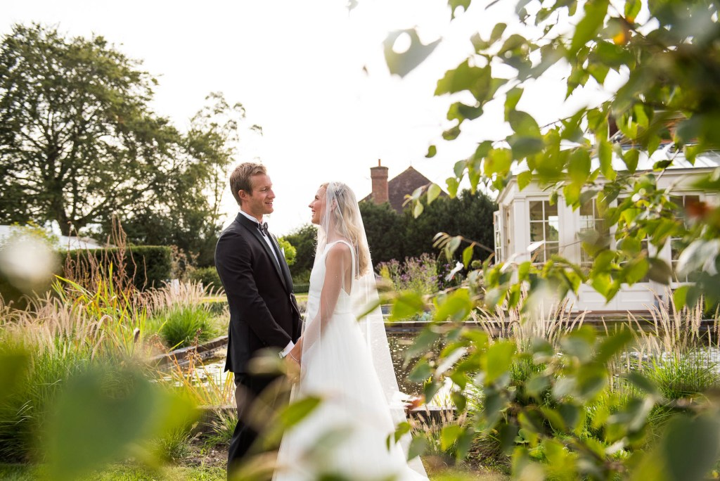 Outdoor Wedding Photography Surrey, Bride and Groom Stare Lovingly At Each Other Bathed in Golden Evening Light, Miss Bush Bridal