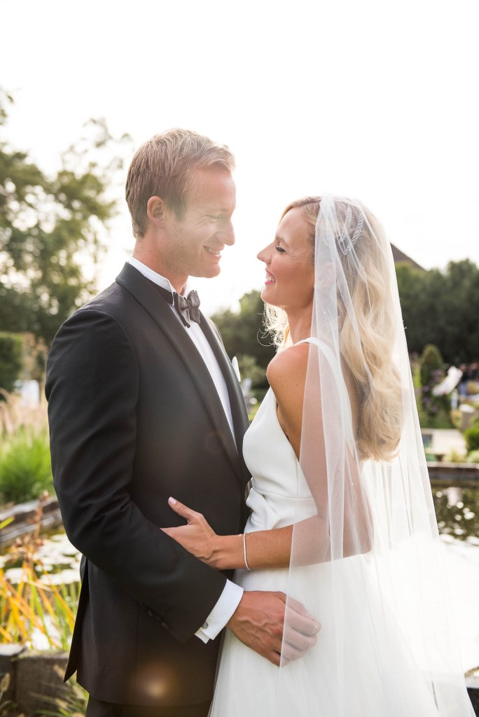 Outdoor Wedding Photography Surrey, Gorgeous Bride With Grace Kelly Style Curls and a Sheer Veil Embraces Her Husband Passionately