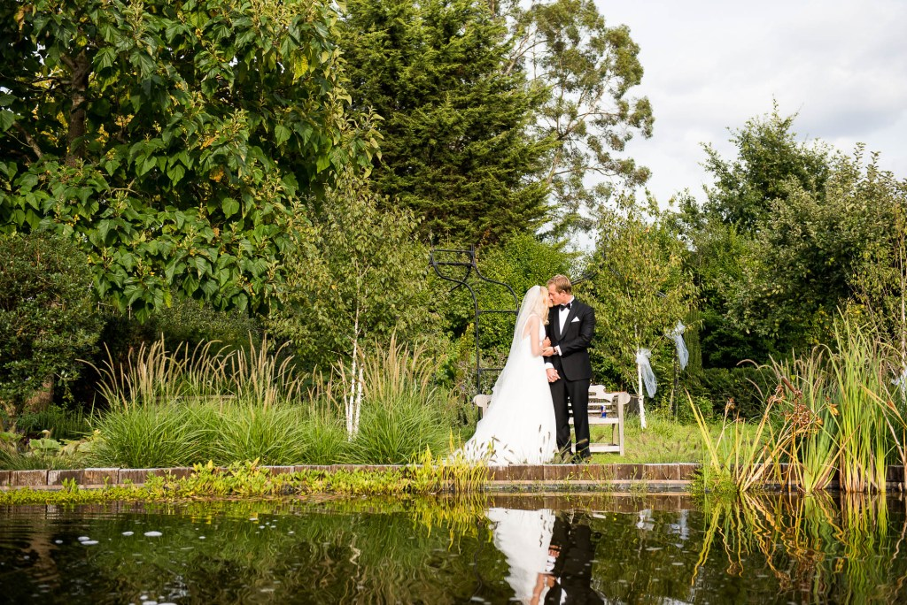 Outdoor Wedding Photography Surrey, Elegant Couple Embrace Each Other As Their Reflection Is Seen In The Lake