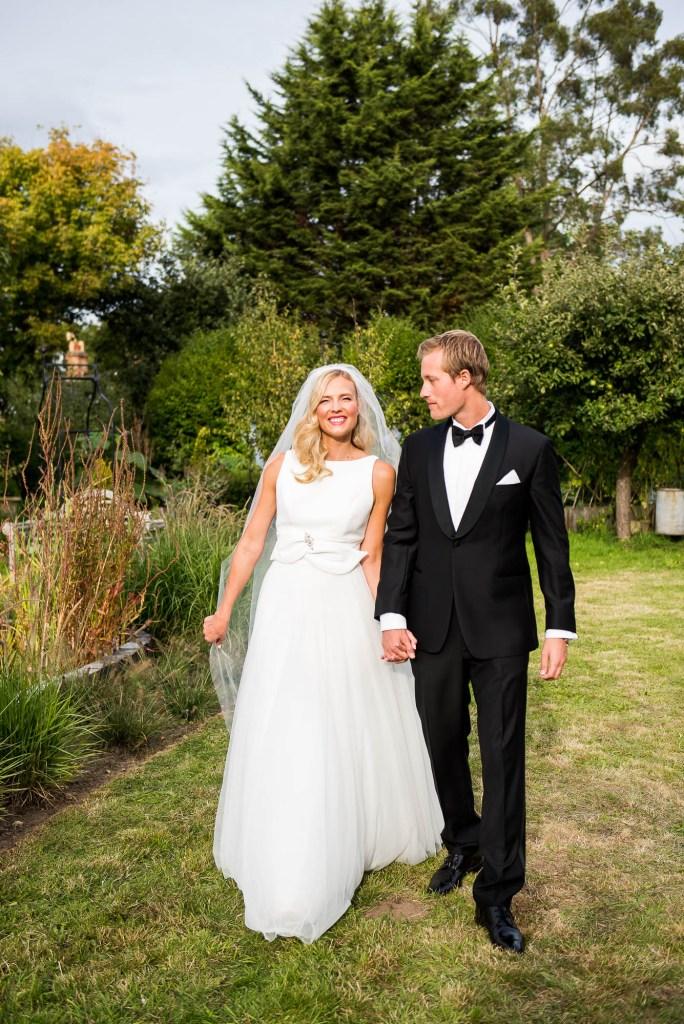 Outdoor Wedding Photography Surrey, Stylish Couple Walking Naturally Hand In Hand at Their Elegant Garden Wedding