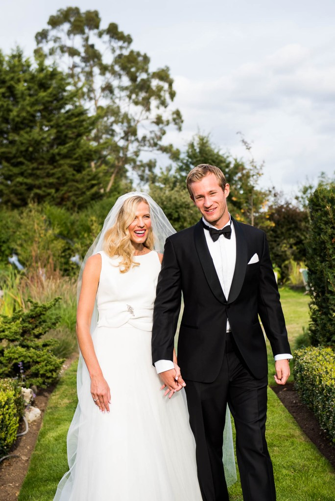Outdoor Wedding Photography Surrey, Elegant Bride and Groom In Black Tie Dress Walking Together and Laughing