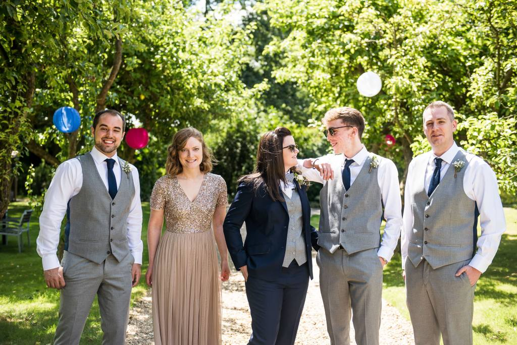 lgbt wedding photographer, Bride stands with her bridal party in a smart tailored suit and bow tie
