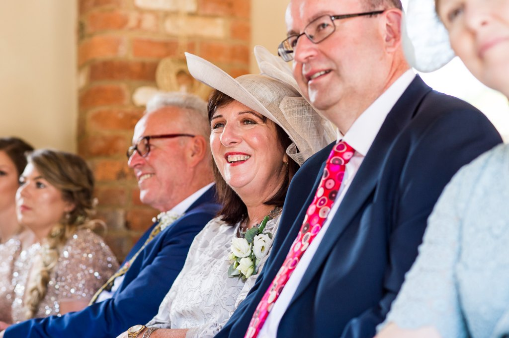 lgbt wedding photographer, Guests smile as brides marry at same sex ceremony
