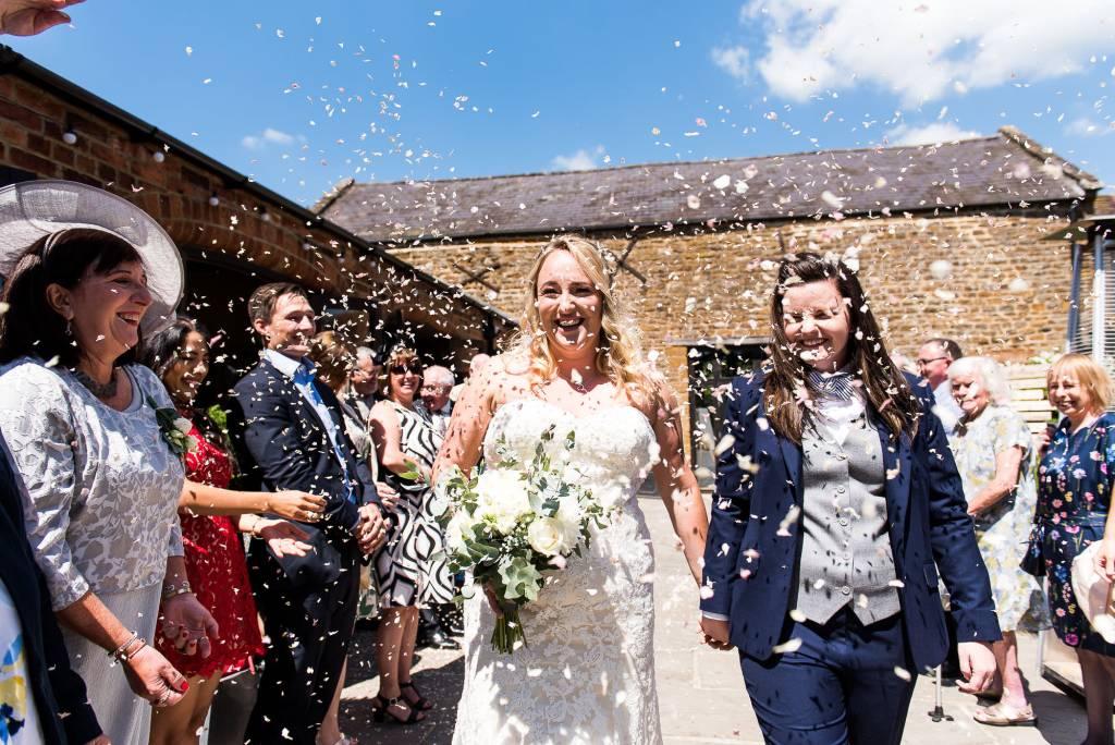 lgbt wedding photographer, brides walk down the confetti aisle at their glorious outdoor wedding