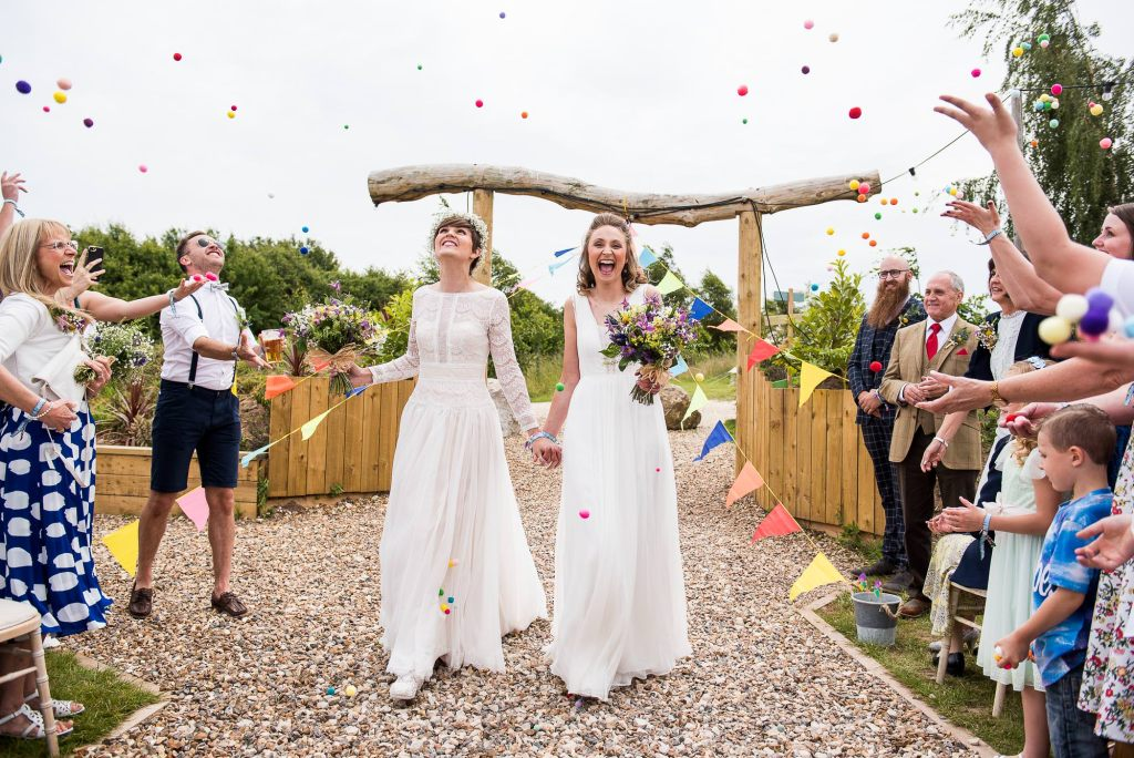 LGBT wedding photography, same sex couple walk down pom pom confetti aisle