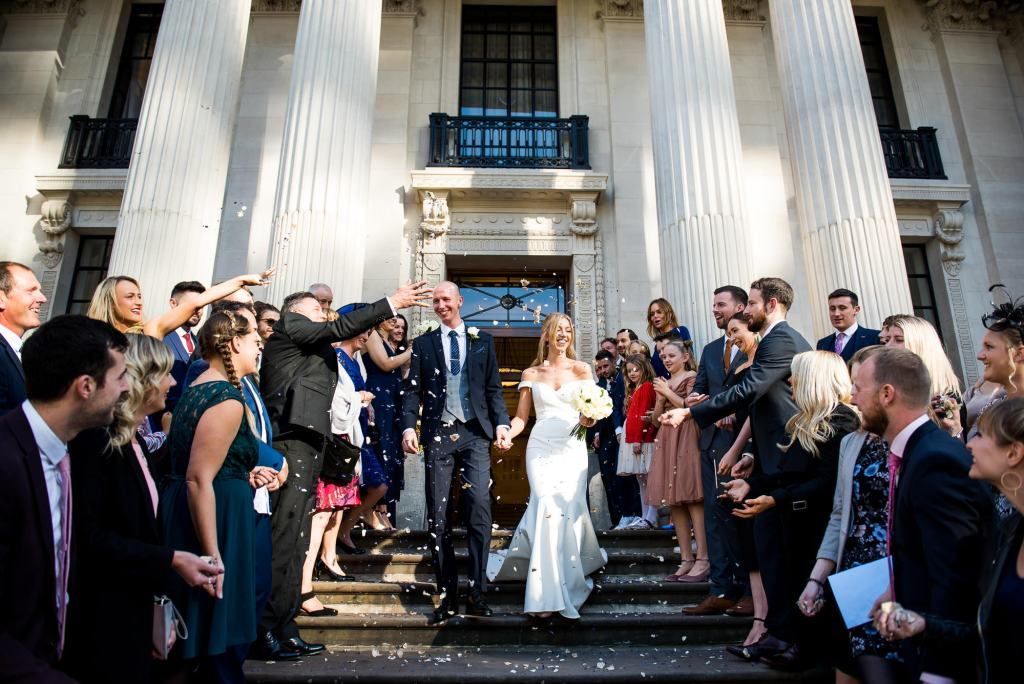 Old Marylebone Town Hall Wedding, stylish bride and groom exit their wedding to confetti line, London wedding